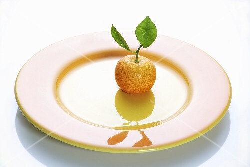 A clementine with leaves on a plate