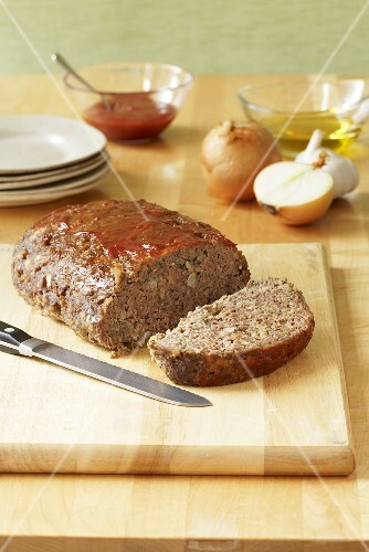 Partially Sliced Meatloaf on Cutting Board; Plates and Ingredients