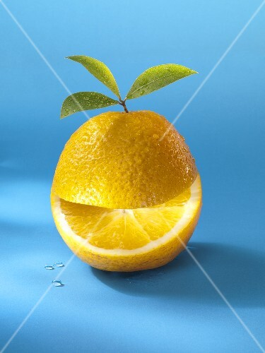A wet orange with leaves and a slice cut out