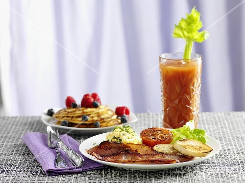 Brunch with bacon, scrambled eggs, pancakes and a tomato drink