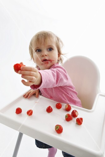 A small child with strawberries