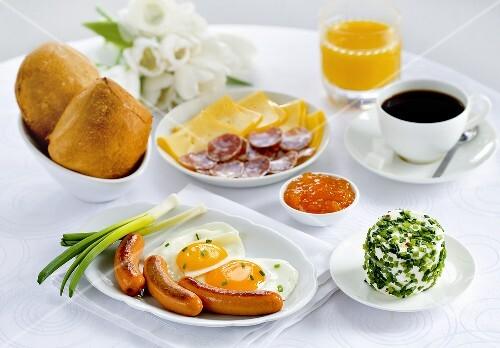 Frühstück mit Würstchen, Spiegelei, Wurst-Käse-Platte, Kaffee, Marmelade