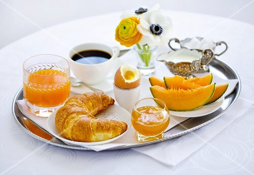 Breakfast with melon, croissant, egg, jam, coffee and orange juice