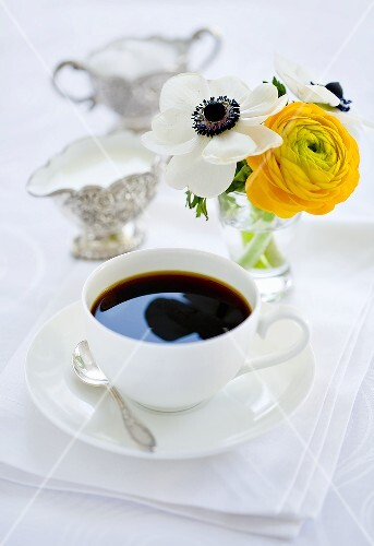 A cup of coffee, milk, sugar and a bunch of flowers