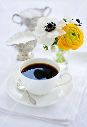 Kaffeetasse, Milch, Zucker und Blumenstrauss