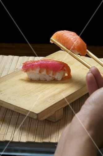Hand holding sushi in chopsticks