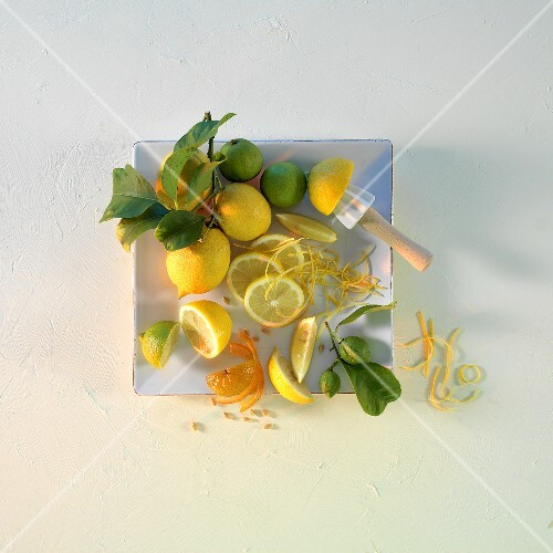 Lemons and limes with leaves on a square plate