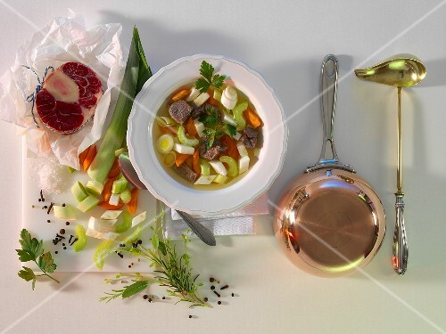 Pot-au-feu with ingredients, a pot and a ladle