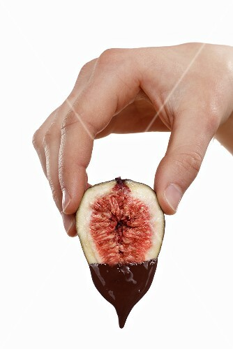 Hand holding a fig dripping with melted chocolate
