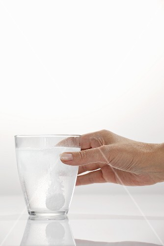 A hand holding a glass with an effervescent tablet