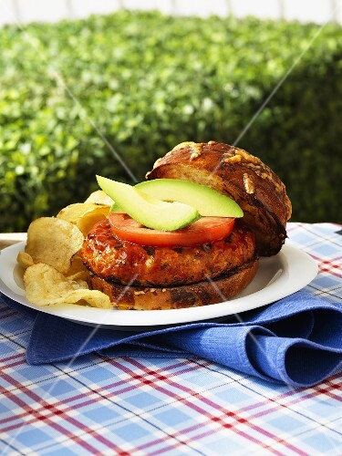 Chicken burger with tomatoes, avocados and potato chips