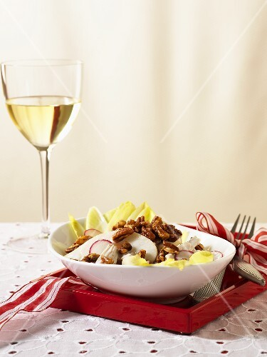 Winter salad with chicory, radishes and nuts and a glass of white wine