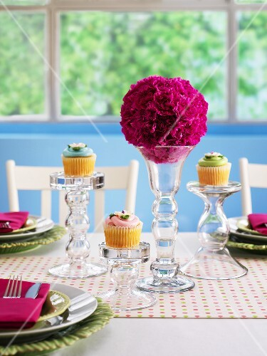 A festively laid table with flower balls and cupcakes