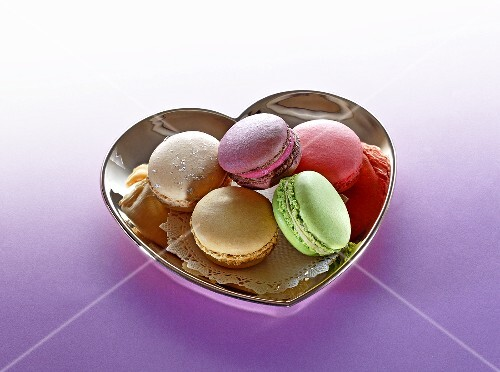 Different types of macaroons in a heart-shaped dish