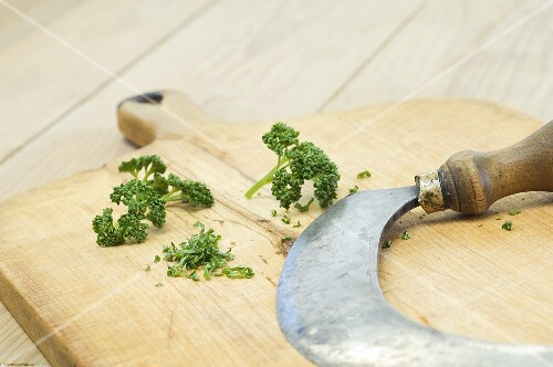 Parsley and chopping knife on a wooden cutting board
