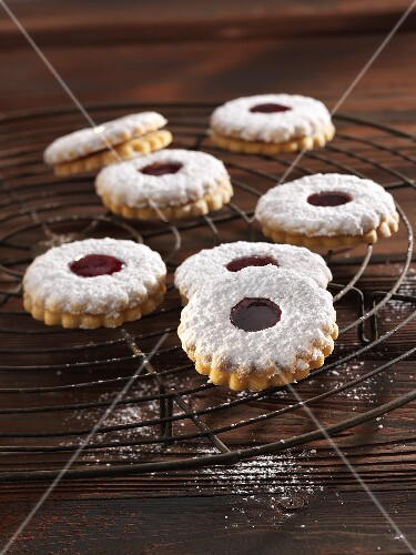 'Spitzbuben' (jelly filled cookies) with powdered sugar on a cooling rack