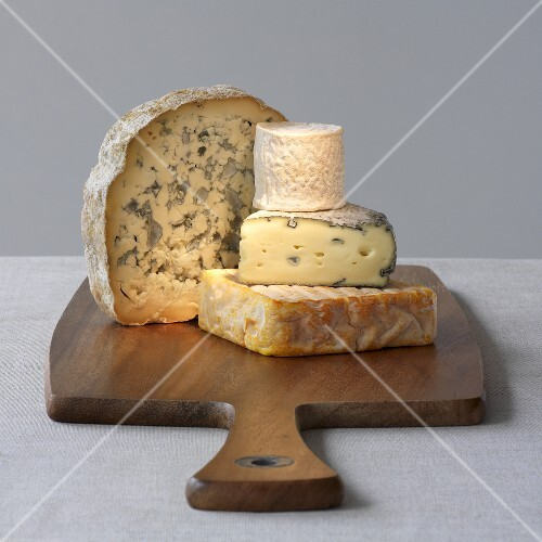 Four varieties of cheese on a wooden board