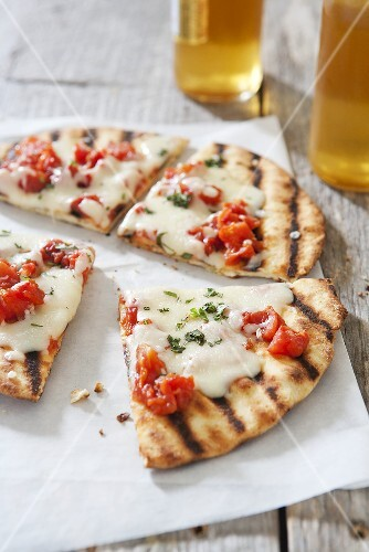 Grilled Mozzarella and Tomato Pizza on an Outdoor Table; Beer