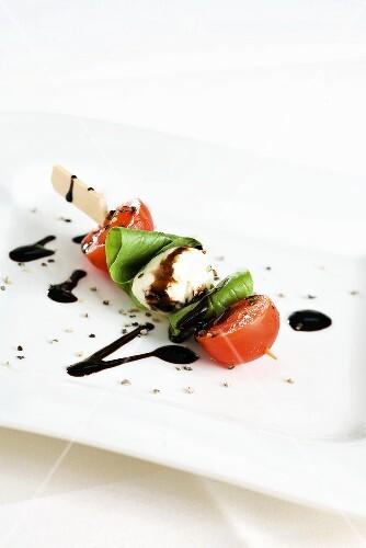 Tomato and mozzarella on a stick with balsamic vinegar