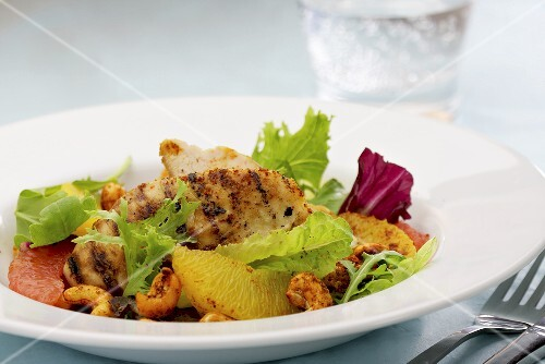 Grilled chicken fillets with citrus fruits, lettuce and cashew nuts