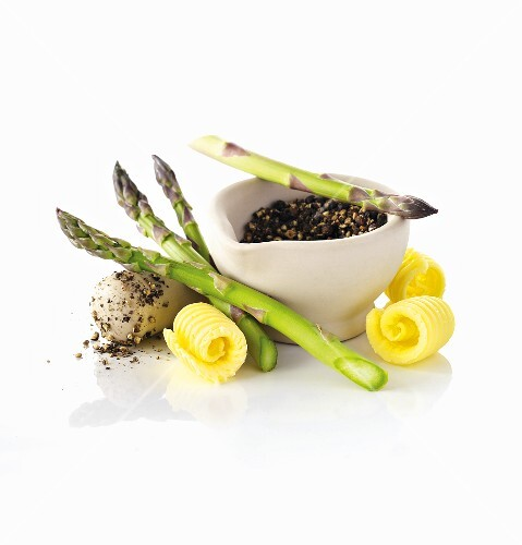 Asparagus, butter curls and peppercorns in a mortar