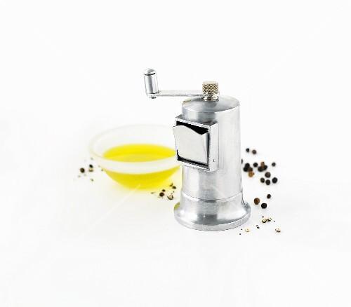 Pepper grinder, peppercorns and olive oil