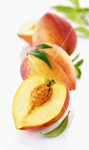 Three white peaches, whole and halved