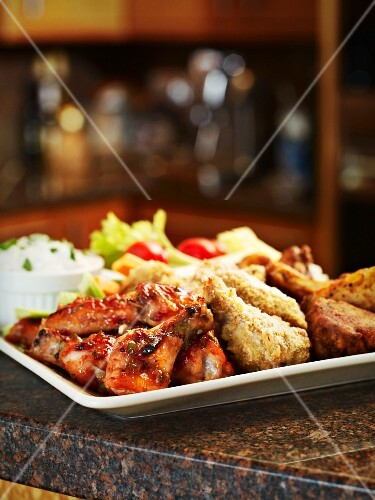 A chicken platter with dips and vegetables