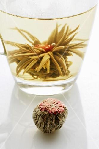 A glass of jasmine tea with a tea rose