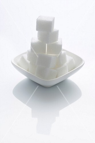 A stack of sugar cubes in a bowl