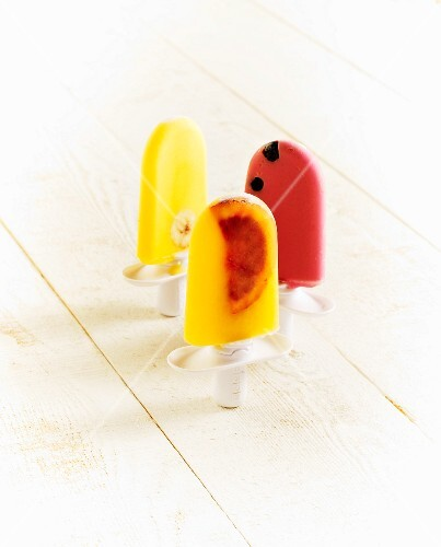 Three homemade ice lollies on a wooden surface