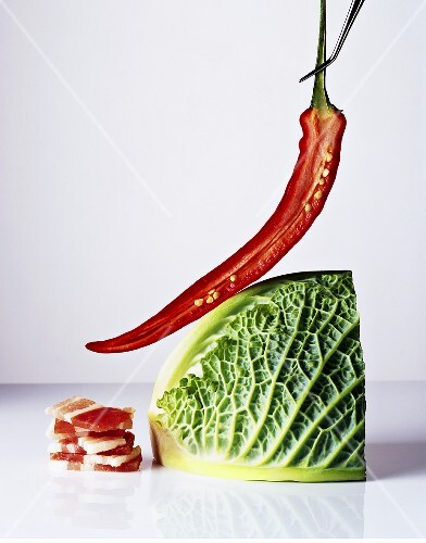 A chilli pepper, bacon and a Savoy cabbage