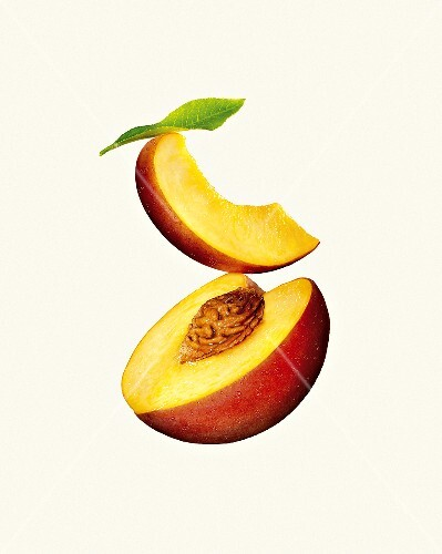 Half of peach and a slice of peach against a white background