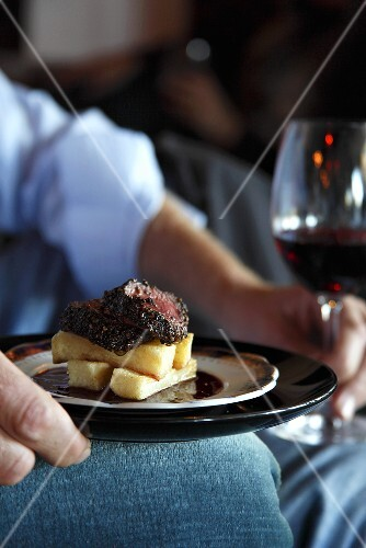 A man holding a plate of ostrich steak and chips and a glass of red wine