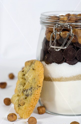A hazelnut biscuit next to a jar of ingredients