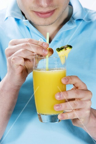 A young man drinking a glass of pineapple juice