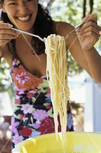 Young woman taking spaghetti out of a plastic colander