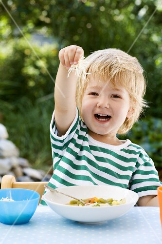 Small boy putting grated cheese into his vegetable soup