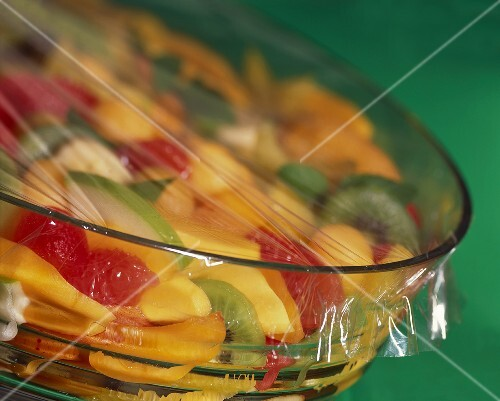 Fruit salad in glass bowl covered with clingfilm