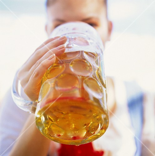 Young woman drinking a litre of beer at October Fest (Munich)