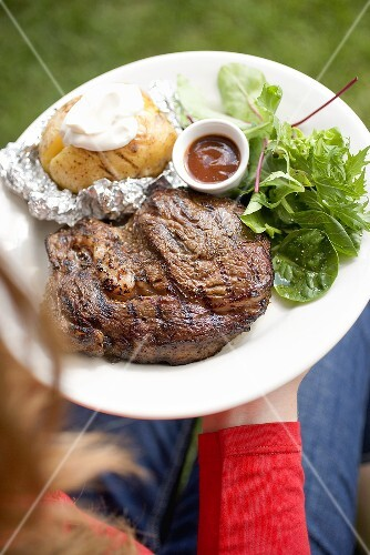Woman holding plate of grilled beef steak & accompaniments