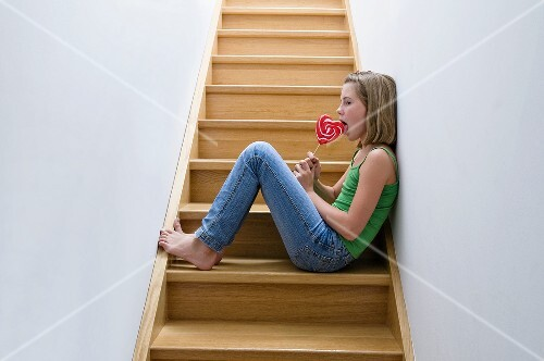 Girl with lollipop sitting on the stairs