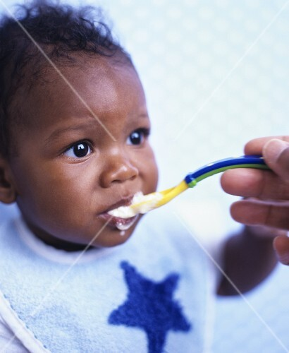 Baby being fed baby cereal