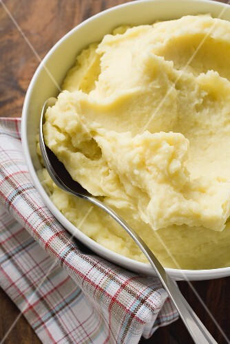 Mashed potato in white bowl with spoon
