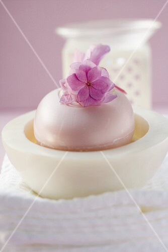 Perfumed soap in soap dish, towels and windlight