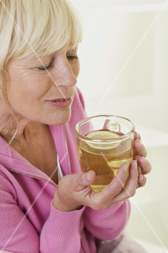 Woman savouring the scent of lemon tea