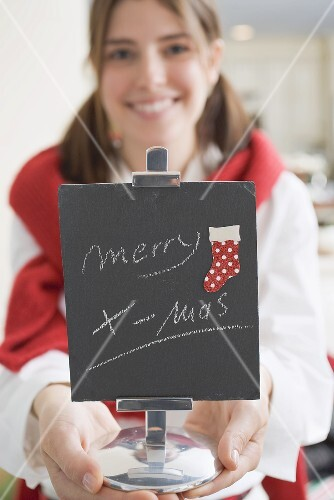 Young woman holding slate with the words Merry X-mas (for table)