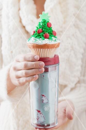 Woman holding cupcake on insulated beaker (Christmas)