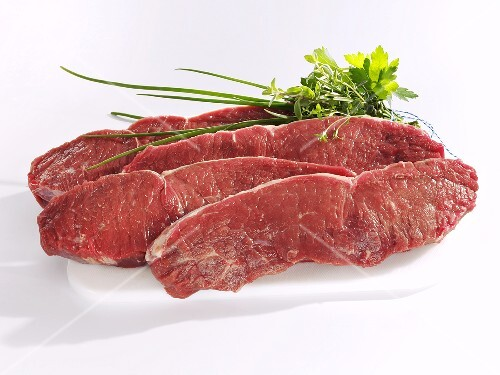 Four sirloin steaks with small bunch of herbs