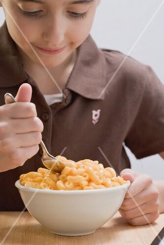 Kleines Mädchen isst Macaroni and Cheese